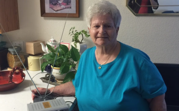 Listener Birdie Knapp with her digital receiver in her home, smiling and looking content.