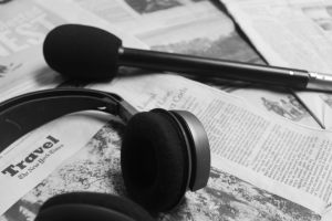 """microphone and padded headphones sitting ontop of scattered newspapers. newspaper text includes: """"Travel: New Your Times"""""""