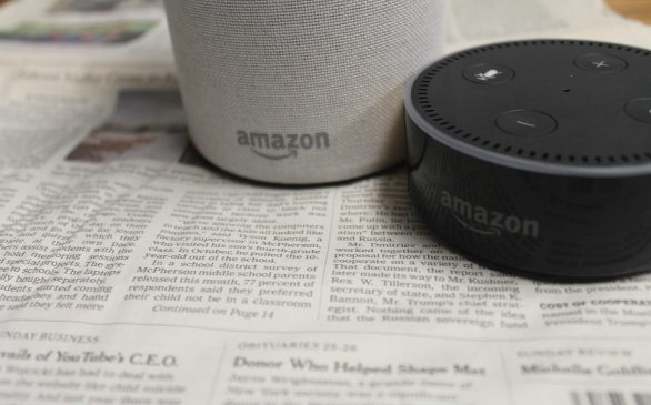 Amazon echo and the echo dot sitting atop of newspapers.