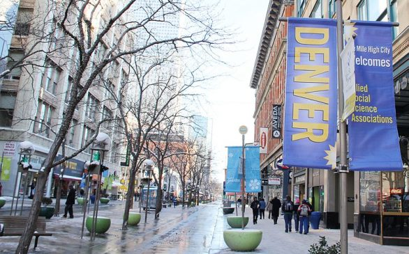 """photo of 16th street mall after a rain. Sign said """"Denver"""", shows trees and streets with people walking."""