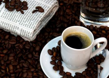 coffee sitting on a small plate covered in coffee beans. coffee beans cover table and a newspaper is visible on the table.