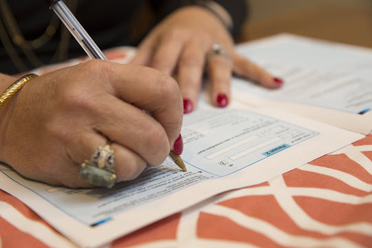 Close up of hands filling in paperwork.