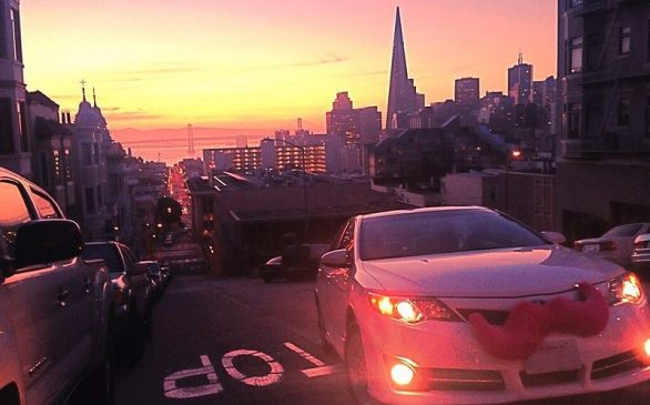 Lyft vehicle driving at sunset with a city in the back ground