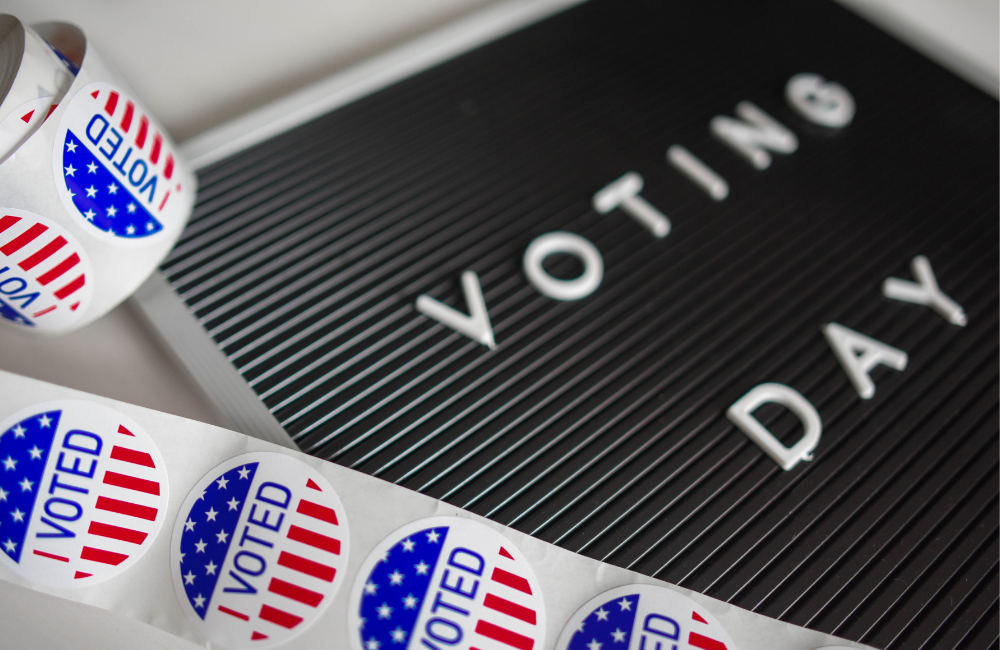 """Close up of reel of """"I Voted"""" stickers on a board that says """"Voting Day"""""""