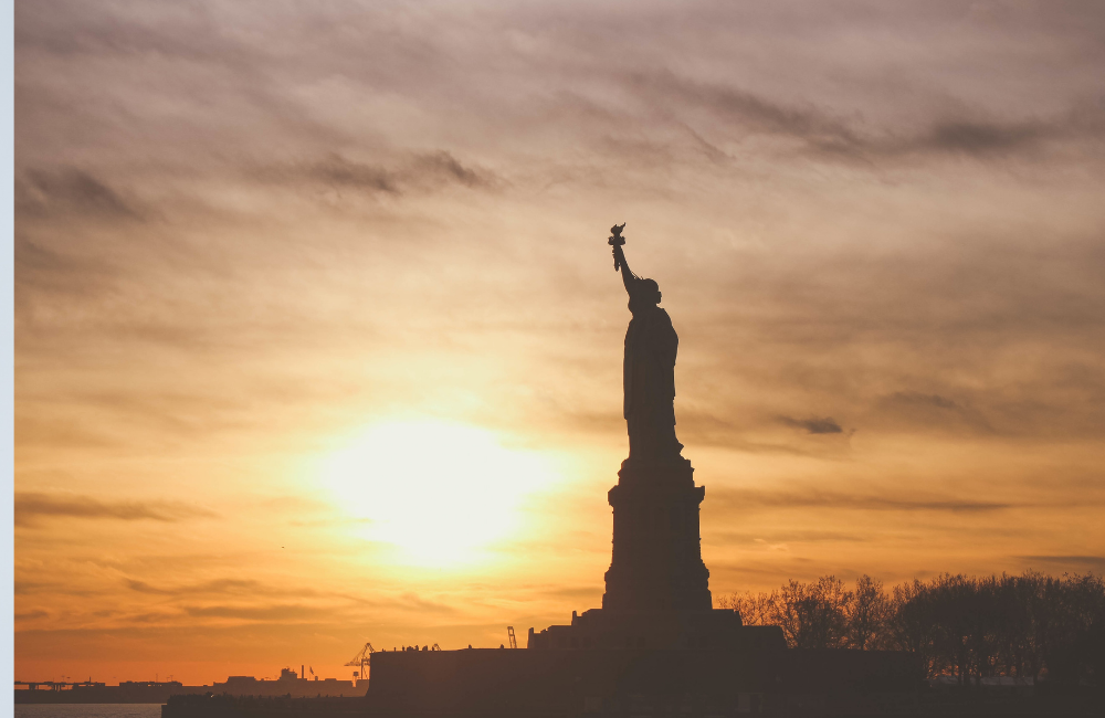 Silhouette of the Statue of Liberty with the sun behind her
