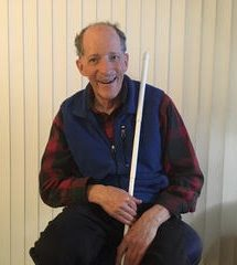 Weinberg sits in a room holding a white cane and smiling.