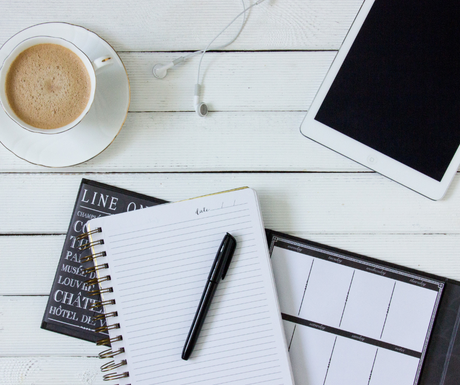 birds eye view of desk with a pen and notepad, a cup of coffee and a smart device.