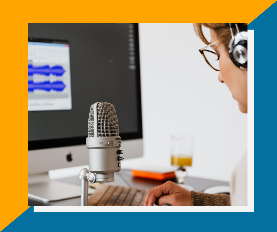 Framed image of a woman sitting infront of a microphone with headphones on, a computer screen in the background displays audio waves in a audio editing software.