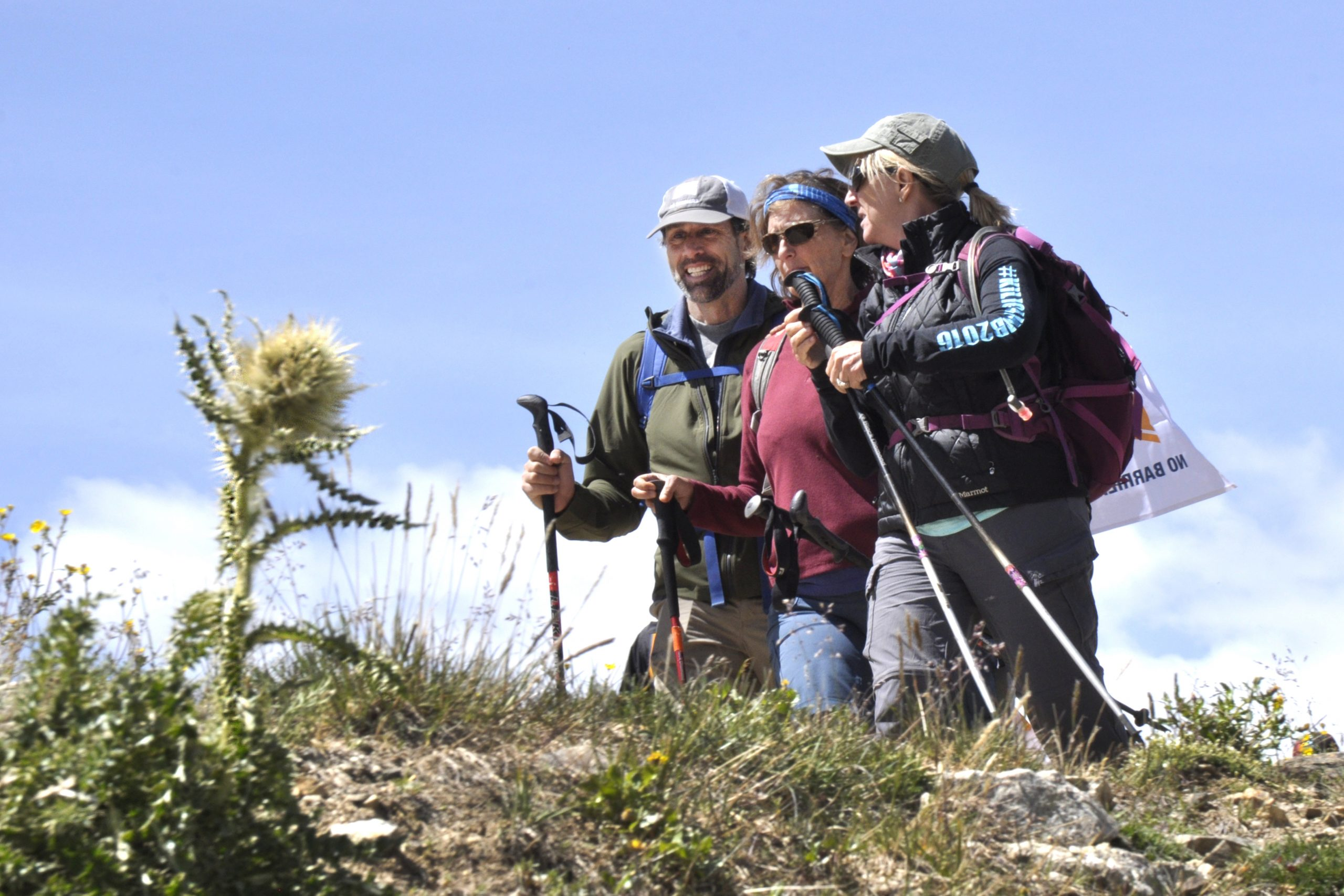 3 Hikers smiling, holding hiking poles.