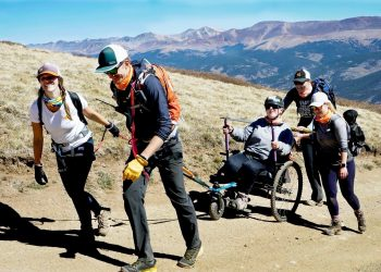 Melissa Simpson in her wheelchair, hiking with her ropes team on a dirt path. Mountain peaks are in the background.