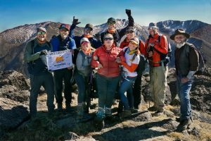 Posed photo of Melissa Simpson and her ropes team at the peak of the mountain, cheering and smiling.