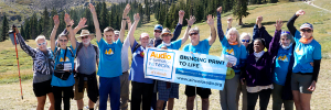 The AINC Hiking team, the AINC Audio Trekkers, standing and cheering in a mountain scene scape holding an AINC Bringing print to Life banner.